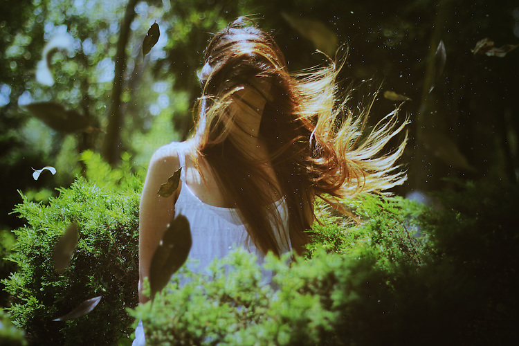 outdoors portrait of a girl among trees and foliage with hair covering her face