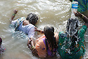 A woman assists her neighbor as she plunges her head beneath the waters of the Ganges River in Varanasi, India while another woman uses a plastic bottle to do the same.