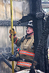 A Menomonee Falls firefighter with a debris pole at a scene of a fire collapsed building