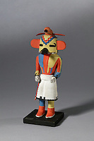 Tootsa katsina by Viets Lomahaftewa, Hopi, Shung-opavi artist, made 1952 from wood, paint and feathers, bought through the Native Arts Acquisition Fund, in the Denver Art Museum, Denver, Colorado, USA. Hopi katsina figures or kachina dolls are figures carved, typically from cottonwood root, by Hopi people to teach girls about katsinas or katsinam, the immortal beings that bring rain and act as messengers between humans and the spirits. The Tootsa katsina is a hummingbird katsina (seen here with the bird on his head) who sings prayers for moisture and dances quickly to encourage rain. The Hopi tribe live in North East Arizona and have been making these katsina figures since the 19th century. Picture by Manuel Cohen