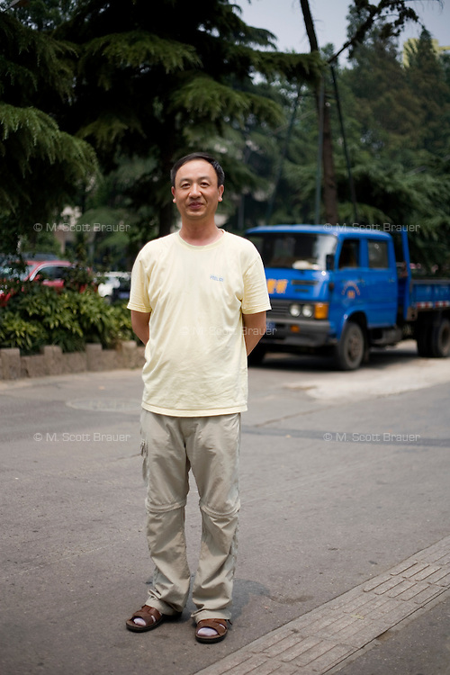 "Yaming, a reporter, age 47, poses for a portrait in Nanjing. Response to 'What does China mean to you?': 'Responsible for hope, power and ""culture.""'  Response to 'What is China's role in the future?': 'To make a bigger contribution to world peace.'"