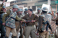 Local police officer being beaten by federal paramilitary police apparently for refusing the paramilitary into the property he was guarding. This happened during confrontation with  stone throwing youth following Friday prayer at the Jamia Masjid mosque.  Srinagar, Kashmir, India. © Fredrik Naumann/Felix Features