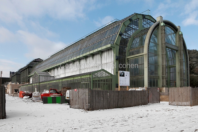 Tropical Rainforest Glasshouse (formerly Le Jardin d'Hiver or Winter Gardens), 1936, René Berger, Jardin des Plantes, Museum National d'Histoire Naturelle, Paris, France. Low angle view of the main Art Deco style glasshouse on a snowy winter day, surrounded by building work.