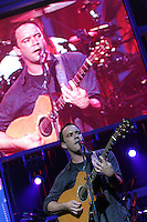 Dave Mathews plays guitar as his image appears on the video screen behind during the sold-out Dave Mathews Band concert at the John Paul Jones Arena Friday in Charlottesville, VA.