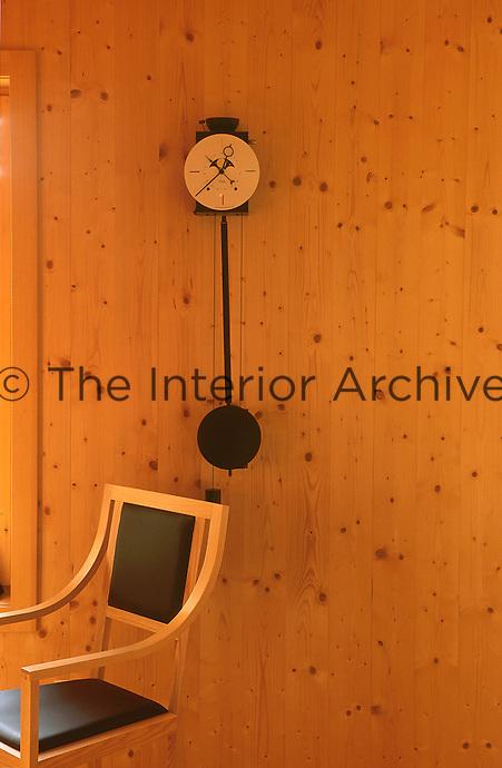 An Odo pendulum clock designed by Armando Baldini hangs on the wall of the dining area