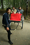 Rickshaws still ply the streets of Arashiyama in the rural part of Kyoto. Nowadays the rickshaw pullers tend to be university students, working at a part-time job rather than this being a blue-collar low level job.  The bamboo grove at Arashiyama, where this rickshaw and passengers is located,  is one of Kyoto's best retreats from the urban scene.