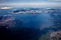 Aerial view of whole Guanabara Bay and surrounding urban areas and remaining mangroves, oceanic bay located in Southeast Brazil in the state of Rio de Janeiro - on its western shore lies the city of Rio de Janeiro (background), and on its eastern shore the cities of Niteroi and Sao Goncalo. Four other municipalities surround the bay's shores. It is the second largest bay in area in Brazil ( after the All Saints' Bay in Bahia), at 412 square kilometres (159 sq mi), with a perimeter of 143 kilometres (89 mi). It is 31 kilometres (19 mi) long and 28 kilometres (17 mi) wide at its maximum. Its 1.5 kilometres (0.93 mi) wide mouth is flanked at the eastern tip by the Pico do Papagaio (Parrot's Peak) and the western tip by Pao de Acucar (Sugar Loaf).