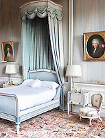Soft hues of blue influence the decoration of this neo-classical style bedroom