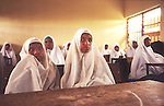 Islamic school for girls and young women in Kano..The implementation of Islamic Sharia Law across the twelve northern states of Nigeria, centres upon Kano, the largest Muslim Husa city, under the feudal, political and economic rule of the Emir of Kano. Islamic Sharia Law is enforced by official state apparatus including military and police, Islamic schools and education, plus various volunteer Militia groups supported financially and politically by the Emir and other business and political bodies. Fanatical Islamic Sharia religious traditions  are enforced by the Hispah Sharia police. Deliquancy is controlled by the Vigilantes volunteer Militia. Activities such as Animist Pagan Voodoo ceremonies, playing music, drinking and gambling, normally outlawed under Sharia law exist as many parts of the rural and urban areas are controlled by local Mafia, ghetto gangs and rural hunters. The fight for control is never ending between the Emir, government forces, the Mafia and independent militias and gangs. This is fueled by rising petrol costs, and that 70% of the population live below the poverty line. Kano, Kano State, Northern Nigeria, Africa
