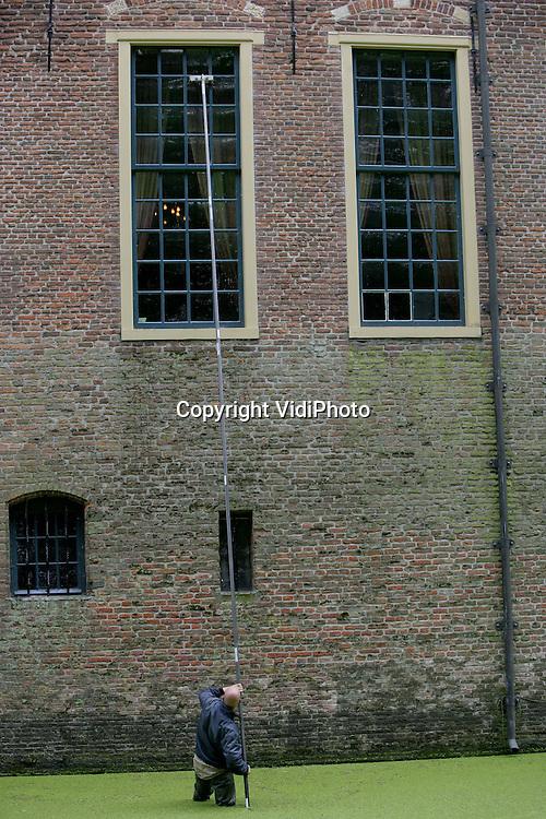 Foto: VidiPhoto..ECHTELD - Wadend door de groene soep in de gracht van kasteel Wijenburg in Echteld, probeert glazenwasser Jean-Paul den Aantrekker uit Valburg voorzien van lieslaarzen en een lange stok de ramen van het middeleeuwse kasteeltje woensdag schoon te krijgen. De klus is bepaald niet zonder gevaar, omdat één misstap de glazenwasser metersdiep doet wegzinken in de gracht. Slechts weinig glazenwassers durven deze arbeidsintensieve klus, die alleen vanuit de gracht uitgevoerd kan worden, aan.