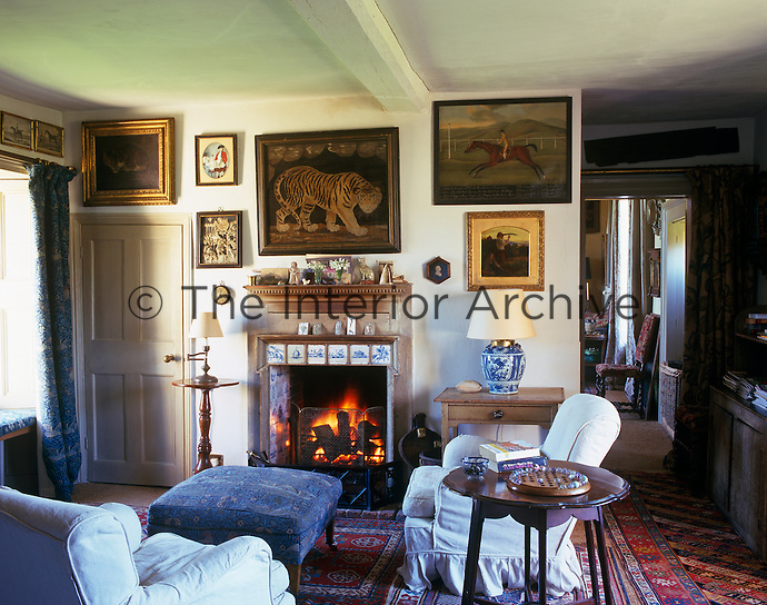 Sporting and equestrian paintings and prints cover the walls of this cosy sitting room which has a roaring log fire