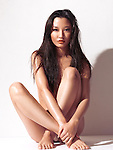 Beautiful young asian woman with bare body sitting in front of a white wall