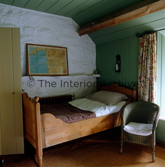 A map of the northern Welsh coast sits on a shelf above the wooden bed in this small guest bedroom