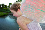 Girl in Angel Costume Dreaming Above Marsh Bay in Levy Park, Merrick, Long Island, NY.  Wood texture