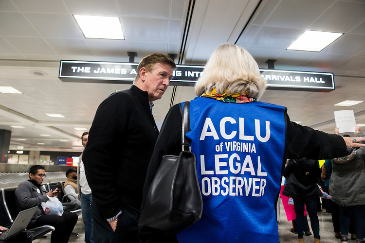 UNITED STATES - JANUARY 29: Rep. Don Beyer, D-Va., speaks with an ACLU legal observer during the protest at Dulles International Airport in Virginia on Sunday, Jan. 29, 2017. Protests erupted at airports around the country following President Trump's executive order restricting travel from several Islamic countries. (Photo By Bill Clark/CQ Roll Call)