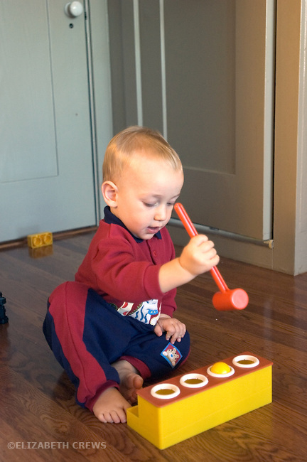 Berkeley CA Boy, sixteen months, using wrong side of hammer to bang balls through holes on hammering toy  MR