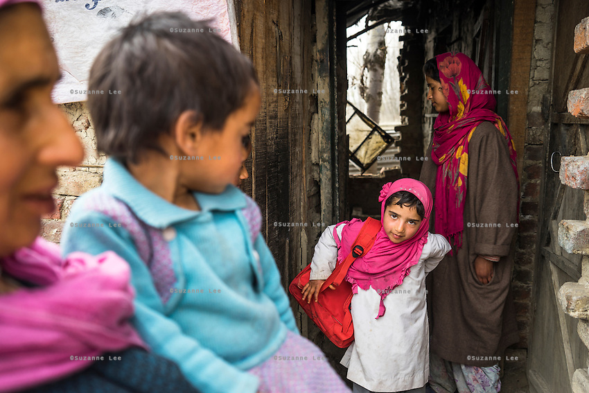 Tasfiya, 16, closes the door as Muskaan, 6, puts on her education kit school bag as she exits her collapsed house in Purnishadashah village, Jammu and Kashmir, India, on 24th March 2015. The family house was destroyed in the floods forcing them to move in with relatives. Save the Children supported the family with kitchen items, hygiene kits, food baskets, blankets, a solar powered lamp and education kits for the children. Photo by Suzanne Lee for Save the Children