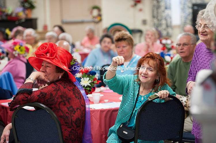 """NAUGATUCK, CT-1 May 2015-050115EC07-  Marion Colella roots for her """"jockey"""" to win during Kentucky Derby Day at the Naugatuck Senior Center. This is the tenth year the senior center marked the Kentucky Derby with it's own friendly competition. Members volunteered to be jockeys and were assigned a horse number. A roll of the dice determined if they advanced to a winning position. The senior center was packed with fancy hats and a Kentucky themed dinner. Members of the U.S. Army handed out roses. Erin Covey Republican-American"""