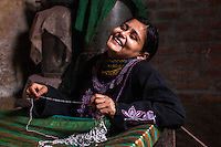 Sultana, aged 16, embellishes a saree in her home in Varanasi, Uttar Pradesh, India on 23 November 2013. Sultana was enticed by a trafficker on the pretext of marriage and was raped repeatedly as he filmed her, using the film to blackmail her as he sold her to another trafficker for INR50000 (USD800). Guria has since put almost all of her traffickers into jail, and has provided her with a grant for livelihood support, which she used to start her saree embellishment business.