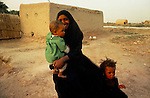 Marsh Arabs. Southern Iraq. Circa 1985. Marsh Arab woman with children and adobe home on banks of river Tigris.
