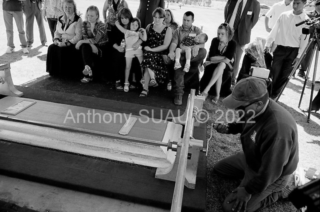 Tucson, Arizona.USA.March 16, 2007..At the Evergreen Cemetery Lori Kasson, the widow of Staff Sgt. Darrel D. Kasson, 43, of Florence, Arizona receives a hug from her 5 year old grand-daughter as she and (to her left) daughter Lisa Varnes (22), and (to her far right) Darrels mother, Sheron Jones, watch as his coffin is lowered into the ground. He died March 4 in Tikrit, Iraq, of wounds suffered when an improvised explosive device detonated near his vehicle at Bayji, Iraq. He was assigned to the 259th Security Forces Company, Phoenix.