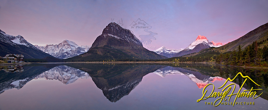 Swiftcurrent Lake sunrise and Panorama. Sunrise at Swiftcurrent Lake in Glacier National Park is a fine place and time  to plant your tripod legs in the morning. Mt. Gould (left) Mt, Grinnell (center) and Mt. Wilbur (right) reaching into the sun cast a nice reflection in the lake as does Swiftcurrent Lodge.