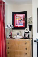 In this bedroom a vintage chest-of-drawers is tucked into an alcove and displays a collection of junk-shop finds including a vintage radio