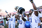 UK's Randall Cobb (left), Allen Moncell (middle), and Winston Guy Jr. (right) hoist the governor's cup after their 23-16 win over Louisville at Papa John's Cardinal Stadium on Saturday, Sept. 4, 2010. Photo by Scott Hannigan | Staff