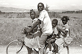 A father gives his children a ride to somewhere in the ountryside outside of Port-au-Prince. photo by jane therese