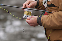 A fly fisherman adds lead sinkers to his line while fishing for steelhead and salmon on the Carp River a Lake Superior tributary near Marquette Michigan in spring.