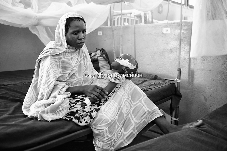 A mother holds her baby, injured in an aerial bomb attack, at a hospital in an undisclosed location in South Kordofan, 5 July 2011. On the 5 June, after almost 10 years of relative peace, Sudan's President Omar Al-Bashir sent his army, the Sudan Armed Forces (SAF), to attack on the people of the Nuba Mountains in South Kordofan, using MiG fighters to shoot at vehicles, and Antonov cargo planes, converted to use as heavy bombers. (John D McHugh)