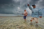 Flyfisherman and guide fishing in shallows at Turneffe Flats Resort, Turneffe Atoll, Belize