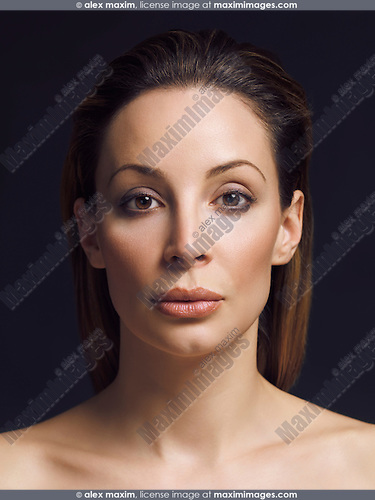 Beauty portrait of a woman with brown hair and clean natural makeup in her early thirties isolated on black background