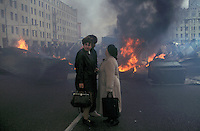 Moscow, Russia, 02/10/1993..Saturday afternoon shoppers look at burning barricades on the city's central ring road. Demonstrators built barricades in the city centre after riot police prevented them from marching to the Russian Parliament, which rebel Communist and nationalist deputies, led by Vice-President Alexander Rutskoi, had occupied after President Boris Yeltsin dissolved the parliament.