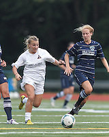 Boston Aztec midfielder Riley Houle (22) on the attack as Seacoast United Phantoms player Allie Day (2) defends. In a Women's Premier Soccer League (WPSL) match, Boston Aztec (white) defeated Seacoast United Phantoms (blue), 3-0, at North Reading High School Stadium on Arthur J. Kenney Athletic Field on on June 25, 2013.