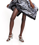Closeup of legs of an african american woman wearing high heel snadals and a summer dress isolated on white background