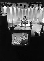 Beatles appear on tv monitor in CBS studios as they perform on Ed Sullivan Show, February 1964, New York. Photographer John G. Zimmerman