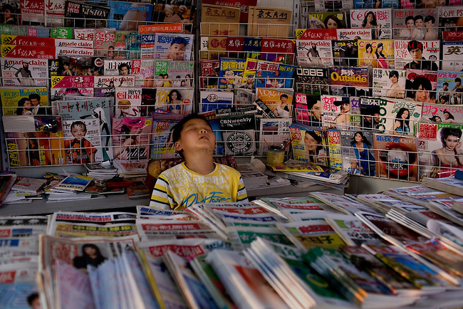 A boy falls asleep at the job behind a news stand in Beijing, China on Tuesday, August 5, 2008. The city of Beijing is gearing up for the opening ceremonies of the Olympic Games.  Kevin German
