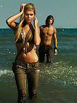 Young woman in army style outfit walking out of water and a young man following her.