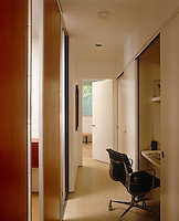 A series of sliding doors conceals a home office situated in a narrow corridor