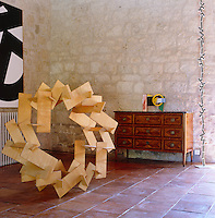 A large circular wooden sculpture by Pierre Clerk juxtaposed with an American chest of drawers in the living room