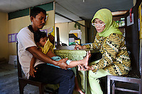 A doctor examining a young child at a small clinic, Makassar, Sulawesi, Indonesia.