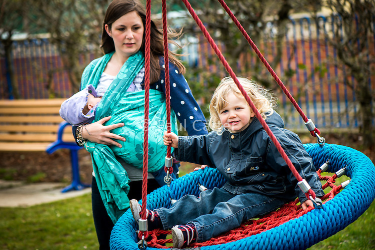 A young mother breastfeeds her baby from a sling while standing up and pushes another older child on a swing in a playground.<br /> <br /> Image from the &quot;We Do It In Public&quot; documentary photography project collection: <br />  www.breastfeedinginpublic.co.uk<br /> <br /> Dorset, England, UK<br /> 17/04/2013