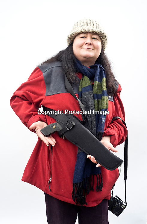 """We just wanted to stand in solidarity with people who share our same belief system regarding the 2nd Amendment,"" said Cathleen Lombard, of Puyallup, while holding the .357 S&W Magnum she received as a 50th birthday gift from her husband, David, three years ago. The Lombards were two of about 1,500 gun owners and supporters to attend the Guns Across America rally at the Washington State Capitol in Olympia Saturday, Jan. 19, 2013. Photo by Daniel Berman/www.bermanphotos.com."