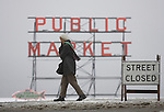 A Seattleite crosses a closed street near Pikes Place Market after a snowstorm hit the Seattle area early Wednesday morning dumping at least 4 to six inches and will likely continue into the afternoon it a tough commute for drivers  in Seattle on January 18, 2012. ( ©2012. Jim Bryant Photo. All Rights Reserved.