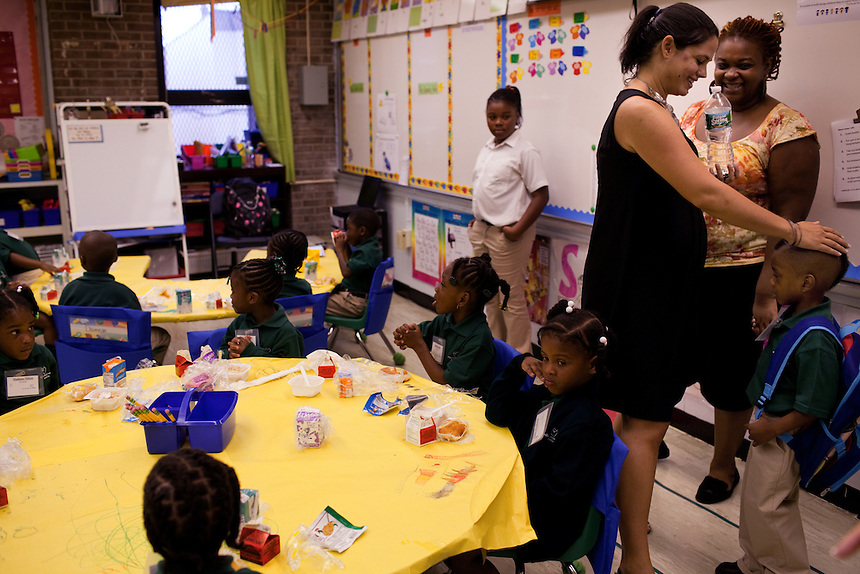 Principal Gina Ribiero greets a new student into kindergarten on the first day of class at Brownsville Elementary School in Brooklyn, NY on August 15, 2011.