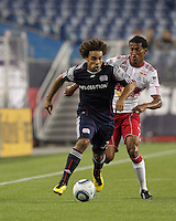 New England Revolution defender Kevin Alston (30) brings the ball forward as New York Red Bulls defender Roy Miller (7) defends. The New England Revolution defeated the New York Red Bulls, 3-2, at Gillette Stadium on May 29, 2010.