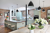 A skylight sits directly above the food-prep area, ensuring the space is well lit when cooking dinner. Pendant lights provide further illumination and match the ones over the table