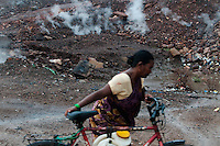 A lady carries drinking water for her home at Bokapahari while posionous gases and fumes coming out of fissures. A huge coal mine fire is engulfing the city of Jharia from all its sides. All scientific efforts have gone in vain to stop this raging fire. This fire is affecting lives of people living in and around Jharia. Jharkhand, India. Arindam Mukherjee
