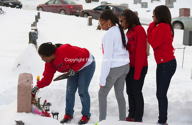 WATERBURY, CT 020714JS12- FEBRUARY 11, 2014_ Tamara Dawkins of Naugatuck, clears off the headstone for her son Torrance Dawkins as family members look on. Tamara along with family and friends, held a graveside vigil at All Saints Cemetery in Waterbury on Tuesday for Torrance Dawkins, who was killed outside a nightclub in New Haven in August. Tamara is frustrated because no arrests have been made six months after the shooting. Jim Shannon Republican-American